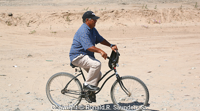 Mexican man's primary mode of transportation is his bicycle.