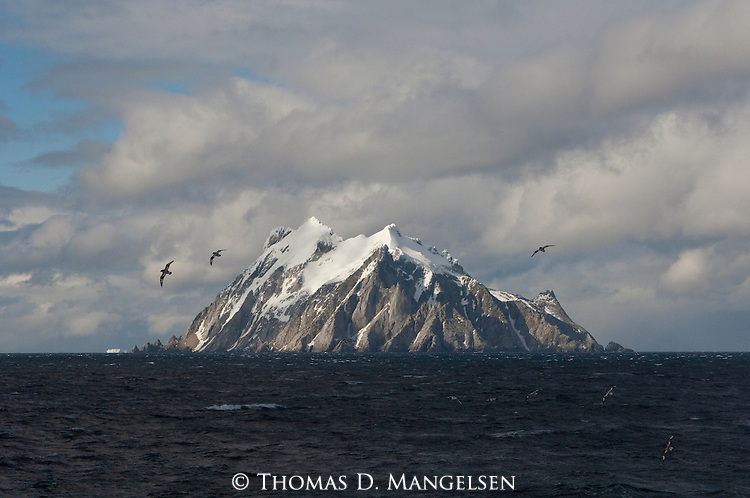 Birds fly around snow-capped Coronation island of the South Orkney Islands.