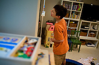 """Jack Ursitti, 7, plays with his reflection in a mirror during a """"sensory break"""" in his home in Dover, Mass., on Monday, July 25, 2011.  Jack has been diagnosed with autism.  After school at his home, Jack works with his teacher and a therapist to do educational and independent leisure activities. Periodically Jack takes """"sensory breaks"""" to stop activity and play independently, allowing him to return to his tasks with greater concentration. During the """"sensory breaks"""" Jack does a variety of things, including looking at his reflection, making faces, jumping on a small trampoline or cushions, or play with an iPad...Jack Ursitti wears a small GPS ankle bracelet at all times in case he runs off from his family or caretakers. The device will be activated if he goes missing, allowing police and other searchers to find him."""