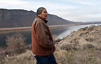 "Rex Buck Jr., leader of the Wanapum Indians is photographed on a hillside surrounded by power lines and the Columbia River behind him on February 3, 2011.   ""The river flows in us and we're a part of the river and we're also a part of this land.""  said Buck. The Wanapum Indians never moved onto a reservation but negotiated peacefully with a power company to remain on their land.  The power company today is the Grant County Public Utility District.  (photo credit Karen Ducey)"