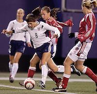 "USA's Mia Hamm looks to split the defense of Denmark's Bettina Falk, and Anne Dot Eggers. The US Women's National Team tied the Denmark Women's National Team 1 to 1 during game 8 of the 10 game the ""Fan Celebration Tour"" at Giant's Stadium, East Rutherford, NJ, on Wednesday, November 3, 2004.."