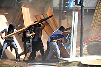 Rioters hide under pieces of wood to protect from a water cannon during severe clashes   near the Congress building while Deputies Chamber was   discussing changes in   retirement legislation