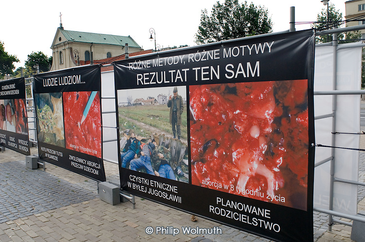 """Anti-abortion posters displayed outside a Catholic church in a central square in the Polish city of Lublin. The first poster reads: """"Ethnic cleansing in former Yugoslavia, abortion at 8 months: same result"""""""