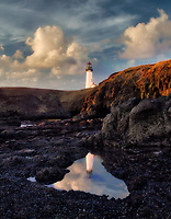 Yaquina Lighthouse with black beach rocks. Oregon.