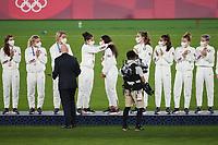 YOKOHAMA, JAPAN - AUGUST 6: Carli Lloyd #10 of the United States places the bronze medal on teammate Christen Press #11 at International Stadium Yokohama on August 6, 2021 in Yokohama, Japan.