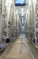 Mas La Chevaliere. near Beziers. Languedoc. Stainless steel fermentation and storage tanks. Cooling coils for temperature control. Pumping wine. France. Europe.