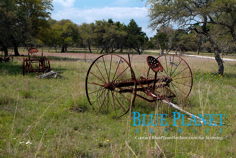 Old and rusty piece of farm machinery abandoned in a field near the city of Fredericksburg, South of Texas, USA