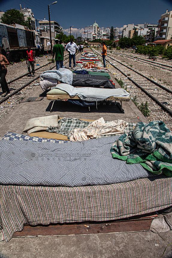 Grecia, Patrasso 2011:rifugiati in un improvvisato campo in una stazione ferroviaria abbandonata. Brandine e materassi per terra sul marciapiede lungo i binari. Grece ville de Patras 2011 - refugies dans une gare abandonnee dormitorio