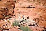 Hearty tourists navigate the rugged red rocks surrounding Horse Shoe Bend.