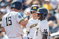 Michigan Wolverines second baseman Ako Thomas (4) celebrates with teammate Jimmy Kerr (15) during Game 11 of the NCAA College World Series against the Texas Tech Red Raiders on June 21, 2019 at TD Ameritrade Park in Omaha, Nebraska. Michigan defeated Texas Tech 15-3 and is headed to the CWS Finals. (Andrew Woolley/Four Seam Images)