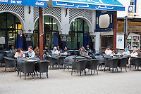 Essaouira, Morocco.  Local Citizens and Tourists Relaxing at Sidewalk Cafe.