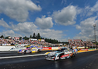 Aug. 7, 2011; Kent, WA, USA; NHRA funny car driver Matt Hagan (near lane) races alongside Ron Capps during the Northwest Nationals at Pacific Raceways. Mandatory Credit: Mark J. Rebilas-