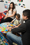 Early Intervention ABA (Applied Behavior Analysis) therapist working with boy at home, mother observing session<br /> ABA is often successful working with children with autism and spectrum disorders