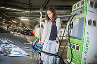 A woman plugs in a electric car to have it recharged. <br />