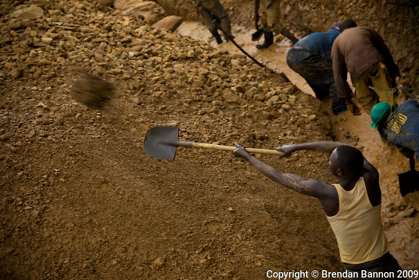 Miners at work near Makala shaft mine. The  men identify abandoned mines and  sift  for residual gold left in the earth..