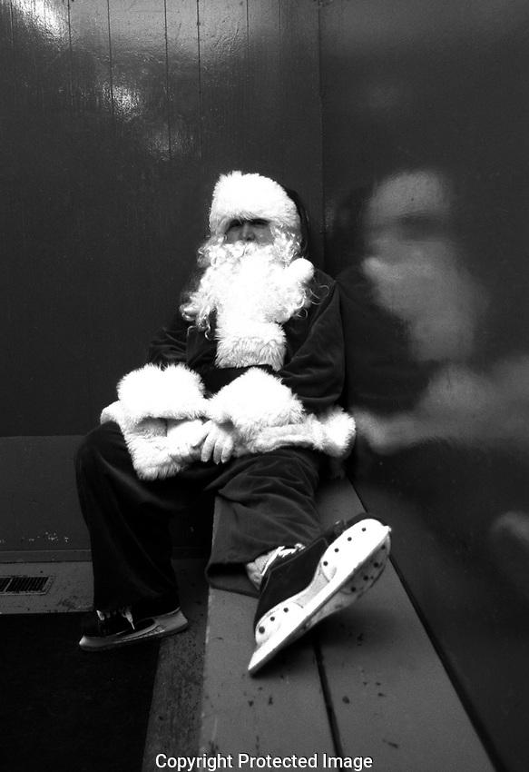 Santa Claus in skates takes a break in the arena dressing room.