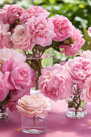 A mass of pink roses is arranged in simple glass tumblers on a garden tabletop in summer