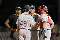 Home plate umpire Ronnie Whiting checks on the status of the conversation between Greenville Drive pitching coach Paul Abbott (48) and his battery of Teddy Stankiewicz (19) and Jordan Weems (18) during the game against the Charleston RiverDogs at Joseph P. Riley, Jr. Park on May 26, 2014 in Charleston, South Carolina.  The Drive defeated the RiverDogs 11-3.  (Brian Westerholt/Four Seam Images)