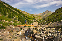Hiker crosses a bridge over a mountain stream on the GR5 long distance foothpath in the Vallon de Sallevieille on the descent from Mont Mounier with Las Donnas in the background.  Parc National du Mercantour. Alpes-Maritimes. Provence, France. Model released.