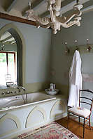 The shape of the neo-gothic window is echoed in the panelling of the bath in this elegant grey-painted bathroom