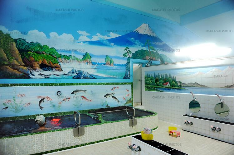 A Japanese woman takes a bath in a Sento, public bath, with the wall painted of Mount Fuji in Tokyo.<br /> <br /> Une Japonaise prend un bain dans un Sento, un bain public, avec le mur peint du mont Fuji à Tokyo. Japon.