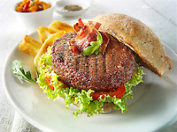 Beef burger with bacon in a wholemeal bun with salad and french fries photo. Funky Stock Photos