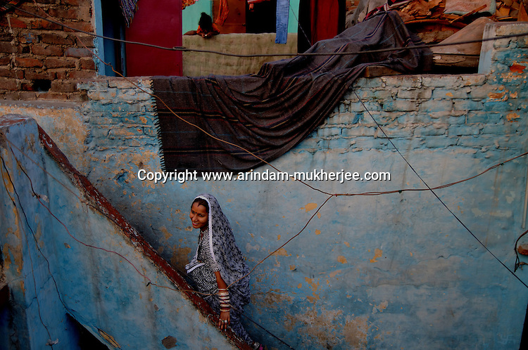 A lady in her house at Katputly colony in New Delhi, India. 14.11.2009. Kathputly colony is a slum area in West Delhi. This slum seems like any other slum areas of modern India with dysfunctional electricity, non existing sanitation and poverty. As a part of Delhi, this is also ailed with water crisis. Large families live their lives crammed together in a single room with all the odds which complement poverty. One thing which differentiates this slum with any other is the people living in the colony. Nearly everybody in this slum is a traditional performing artist; and they have been migrating to this area for last 50 years from different parts of the country for a better livelihood. They are magicians, acrobats, jugglers, puppeteers, dancers and musicians. These artistes perform in star rated hotels, marriage ceremonies of the richer section, functions, and festivities all around the country and the world. Most of the artisans I met here, have performed in Europe and America but such opportunities are rare to come by. They struggle to keep their art form alive. They say that they don't get any help or support from the government for their basic needs and for the well being of the Kathputly colony -  though they have uphold the prestige of the country internationally. Polluted air, dirty alleys smelling of urine, colourful dress and sound of music characterise Kathputly colony, which is the one of its kind in India. Arindam Mukherjee
