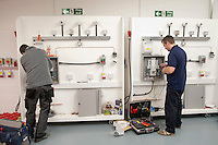 Electricians wiring up new equipment in the Renewables section at the Able Skills Training Centre, Dartford, Kent.