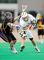 10 April 2011: University of Vermont Catamount attacker A.J. Masson, a Sophomore from Newmarket, Ontario, is checked by University at Albany Great Dane midfielder Matt Mackenzie, a Sophomore from Stony Plain, Alberta, during game action on Moulton Winder Field in Burlington, Vermont. The Catamounts defeated the visiting Danes 11-6 in America East play. Mandatory Credit: Ed Wolfstein Photo
