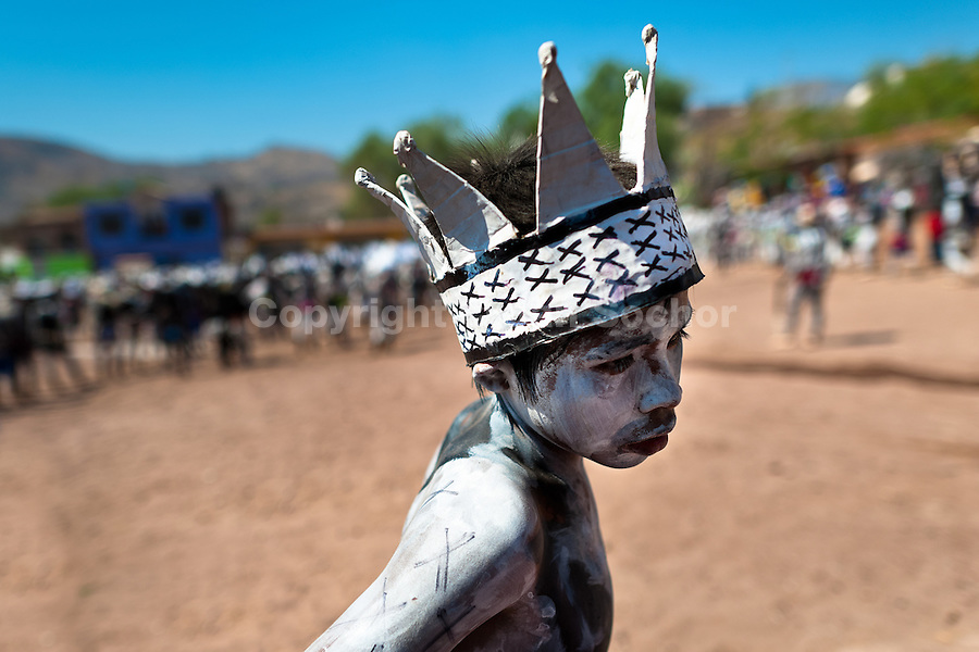 """A Cora Indian boy, wearing a paper crown, dances during the sacred ritual celebration of Semana Santa (Holy Week) in Jesús María, Nayarit, Mexico, 21 April 2011. The annual week-long Easter festivity (called """"La Judea""""), performed in the rugged mountain country of Sierra del Nayar, merges indigenous tradition (agricultural cycle and the regeneration of life worshipping) and animistic beliefs with the Christian dogma. Each year in the spring, the Cora villages are taken over by hundreds of wildly running men. Painted all over their semi-naked bodies, fighting ritual battles with wooden swords and dancing crazily, they perform demons (the evil) that metaphorically chase Jesus Christ, kill him, but finally fail due to his resurrection. La Judea, the Holy Week sacred spectacle, represents the most truthful expression of the Coras' culture, religiosity and identity."""