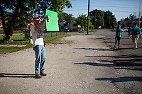 """A community leader pumps up members at the start of """"Circle the City with Service,"""" the Kiwanis Circle K International's 2015 Large Scale Service Project, on Wednesday, June 24, 2015, in Indianapolis. (Photo by James Brosher)"""