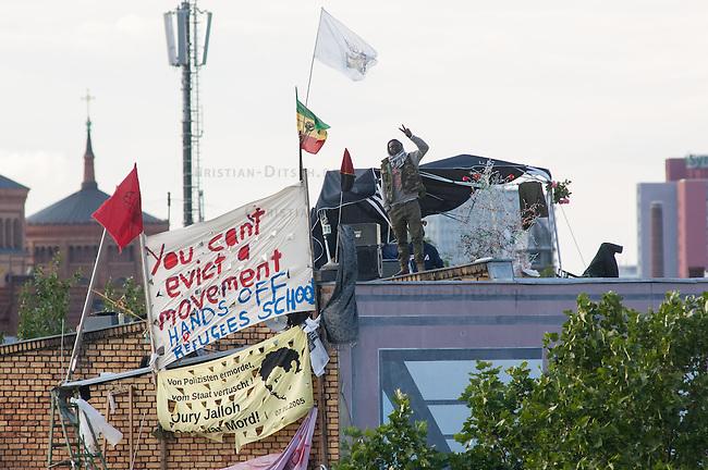 """Fluechtlingsprotest auf dem Dach der Gerhard-Hauptmann-Schule in der Ohlauer Strasse in Berlin-Kreuzberg.<br /> Seit dem 24. Juni 2014 haben harren Fluechtlinge und deren Unterstuetzer auf dem Dach der Gerhard-Hauptmann-Schule aus. Sie hatten sich geweigert dem sog. """"Freiwilligen Umzug"""" zu folgen, der vom Gruenen Bezirksstadtrat Hans Panhoff angeordnet worden war. Die Polizei war bei der als """"Umzug"""" geschoenten Raeumung mit gezogenen Maschinenpistolen angerueckt.<br /> Baustadtrat Panhoff hat am 1. Juli 2014 die polizeiliche Raeumung des Schulgebaeudes beantragt. Einige der Fluechtlinge haben angekuendigt, im Fall der Raeumung vom Dach zu springen. """"Wir haben nichts mehr zu verlieren!"""" sagen sie.<br /> Die Polizei hat seit dem 24. Juni mit ueber 1.000 Beamten saemtliche Strassen um die Schule abgeriegelt. Anwohner duerfen nur nach Personalienfeststellung in ihre Wohnungen, Geschaefte und Gewerbe koennen keine Kundschaft mehr empfangen. Anwohner die gegen das Vorgehen der Polizei protestieren werden von Beamten drangsaliert, geschlagen und verletzt. Mehrere Personen, darunter auch Kinder mussten zum Teil mit Kieferbruch ins Krankenhaus.<br /> Am Abend des 2. Juli 2014 konnte eine Einigung zwischen Fluechtlingen und Bezirksamt eine Einigung erziehlt werden, die den Fluechtlingen einen Verbleib im Hause garantiert. Daraufhin wurden die Polizeimassnahmen beendet.<br /> Im Bild: Blick auf das Dach der besetzten Schule.<br /> 2.7.2014, Berlin<br /> Copyright: Christian-Ditsch.de<br /> [Inhaltsveraendernde Manipulation des Fotos nur nach ausdruecklicher Genehmigung des Fotografen. Vereinbarungen ueber Abtretung von Persoenlichkeitsrechten/Model Release der abgebildeten Person/Personen liegen nicht vor. NO MODEL RELEASE! Don't publish without copyright Christian-Ditsch.de, Veroeffentlichung nur mit Fotografennennung, sowie gegen Honorar, MwSt. und Beleg. Konto: I N G - D i B a, IBAN DE58500105175400192269, BIC INGDDEFFXXX, Kontakt: post@christian-ditsch.de<br /> Urheberverm"""
