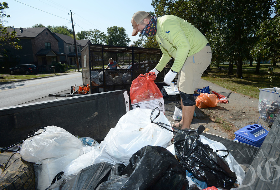 Tyler Anderson, a watershed engineer with the Watershed Conservation Resource Center in Fayetteville, unloads bags of trash collected Saturday, Sept. 26, 2020, by volunteers during the 15th annual West Fork of the White River Cleanup. The event, which was hosted by the Beaver Watershed Alliance as a part of the larger Great Arkansas Cleanup, featured an online registration and group-size limitations because of the current pandemic. Visit nwaonline.com/200927Daily/ for today's photo gallery. <br /> (NWA Democrat-Gazette/Andy Shupe)