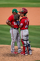 Washington Nationals pitcher Steven Fuentes (58) talks with catcher Tres Barrera (38) during a Major League Spring Training game against the New York Mets on March 18, 2021 at Clover Park in St. Lucie, Florida.  (Mike Janes/Four Seam Images)