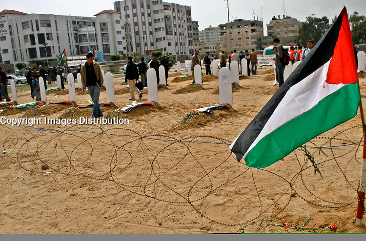 """A Palestinian  works at a fake cemetery to represent the diminishing number of factories in Gaza, during a protest calling for an end of the Israeli siege to the Gaza Strip March 18, 2008.""""photo by Fady Adwan"""""""