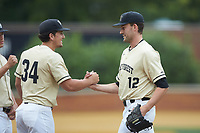 Wake Forest Demon Deacons relief pitcher Tyler Witt (12) is greeted by teammate Bobby Hearn (34) as he comes out of the game against the Miami Hurricanes at David F. Couch Ballpark on May 11, 2019 in  Winston-Salem, North Carolina. The Hurricanes defeated the Demon Deacons 8-4. (Brian Westerholt/Four Seam Images)
