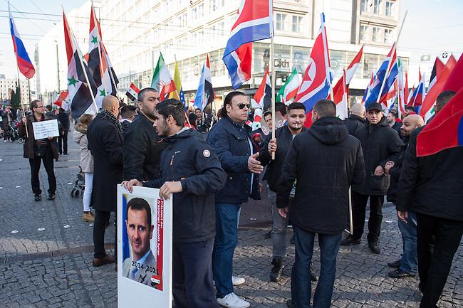 """250 bis 300 Menschen demonstrierten am Samstag den 31. Oktober 2015 in Berlin fuer die Unterstuetzung des syrischen Diktators Assad durch Russland. Sie trugen Fahnen Syriens, der ehemaligen Sowietunion, Russlands, Nordkoreas, der DDR, des Iran und Venezuelas, die sich """"alle zusammen gegen den Imperialismus zur Wehr setzen"""" wuerden. Russlands Praesident Putin wurde ausdruecklich fuer sein Militaerengagement gedankt, das Eingreifen der USA verurteilt.<br /> Im Bild: Demonstrationsteilnehmer mit Nord Korea-Fahnen.<br /> 31.10.2015, Berlin<br /> Copyright: Christian-Ditsch.de<br /> [Inhaltsveraendernde Manipulation des Fotos nur nach ausdruecklicher Genehmigung des Fotografen. Vereinbarungen ueber Abtretung von Persoenlichkeitsrechten/Model Release der abgebildeten Person/Personen liegen nicht vor. NO MODEL RELEASE! Nur fuer Redaktionelle Zwecke. Don't publish without copyright Christian-Ditsch.de, Veroeffentlichung nur mit Fotografennennung, sowie gegen Honorar, MwSt. und Beleg. Konto: I N G - D i B a, IBAN DE58500105175400192269, BIC INGDDEFFXXX, Kontakt: post@christian-ditsch.de<br /> Bei der Bearbeitung der Dateiinformationen darf die Urheberkennzeichnung in den EXIF- und  IPTC-Daten nicht entfernt werden, diese sind in digitalen Medien nach §95c UrhG rechtlich geschuetzt. Der Urhebervermerk wird gemaess §13 UrhG verlangt.]"""
