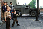 Ireland The Troubles. Belfast young boy with toy gun. British soldier patrols street behind. Downtown urban shopping street Belfast. 1980s. The vechicle, is an armoured personnel carrier,  a  Humber 1 Ton (Pig).<br />