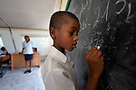 A boy does math on a chalkboard during class at the Notre Dame de Petits school in Port-au-Prince, Haiti. The school's building collapsed in the January 2010 earthquake, and while some classes are conducted in the ruins, other classes meet in large tents provided by International Orthodox Christian Charities.