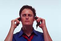 A stressed, cross-eyed young professional man represents The Cellular Age with one phone to each ear.