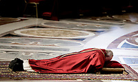 Pope Francis lies down in prayer during the Good Friday Passion of Christ Mass inside St. Peter's Basilica, at the Vatican, Friday, March 30, 2018<br />