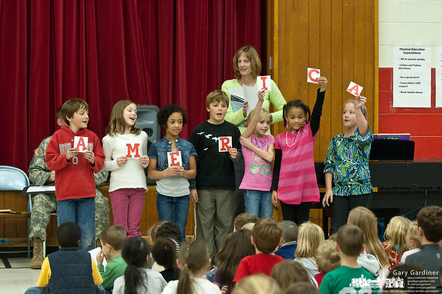 School children hold small cards spelling America after their patriotic presentation for Veterans Day at Cherrington Elementary in Westerville, Ohio. The students gathered in the auditorium to listen to two U.S.Army soldiers talks about their experiences and presented gifts to the two men.
