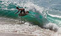 A skimboarder riding shorebreak waves at Ka'anapali Beach, Maui.