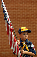 A young Cub Scout carries the American flag during a pack ceremony.