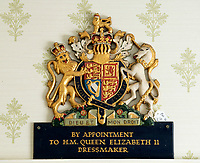 BNPS.co.uk (01202 558833)<br /> Pic: PhilYeomans/BNPS<br /> <br /> The crest that Thomas proudly displayed in his shop in London.<br /> <br /> A remarkable 'timewarp' archive amassed by a dressmaker to the Queen has sold for over £100,000.<br /> <br /> The late Ian Thomas meticulously kept his fashion designs, letters, cards and photographs relating to the Queen at his home that was more like a museum. <br /> <br /> He helped design the Queen's coronation gown in 1953 as well as the powder blue outfit she wore for Charles and Diana's wedding in 1981.<br /> <br /> The lifelong bachelor passed away in 1993 and left his home and its contents to a florist he had been good friends with for 25 years.<br /> <br /> After she died in 2015 the property was inherited by a relative who also knew Mr Thomas well.<br /> <br /> She has now sold the contents at auction.