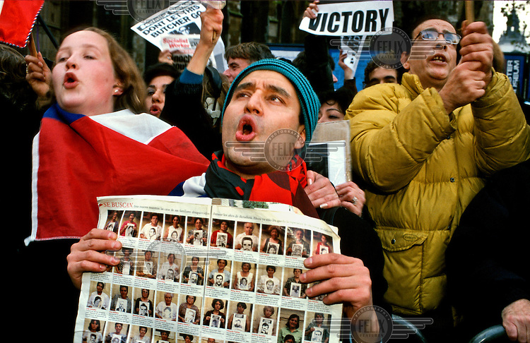 A man displays a magazine article featuring portraits of the relatives of 'disapeared' people each holding a photograph of one of the missing during a rally, by Chilean expats in London, to celebrate the arrest of former dictator Gen. Pinochet.