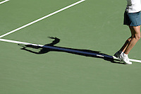 A shadow of a woman and her legs on the tennis court about to serve.