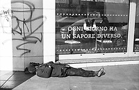 "Milano, periferia nord. Un senzatetto, scalzo, dorme davanti alla vetrina di un ristorante con la scritta ""ogni giorno ha un sapore diverso"" --- Milan, north periphery. A homeless, barefoot, sleeping on the ground in front of the window of a restaurant with the writing ""every day has a different taste"""