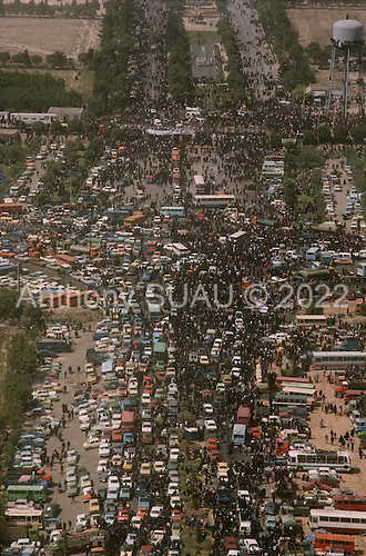 """Tehran, Iran .June 6, 1989..Mourners move towards the burial site for the funeral for the Grand Ayatullah Sayid Ruhullah Musawi Khomeini at the Beheht-E-Zahra cemetery. His body is flown in by helicopter to this site but frenzied crowds prevent the first attempt to bury him. Late in the day, after some of the crowds were cleared, he is buried at this site. He died of heart attack on June 3, 1989...Khomeini was a senior Muslim cleric, Islamic philosopher and marja (religious authority), and the political leader of the 1979 Iranian Revolution that saw the overthrow of Mohammad Reza Pahlavi, the last Shah of Iran. Following the revolution, Khomeini became the country's Supreme Leader?the paramount political figure of the new Islamic Republic...Khomeini was a marja al-taqlid, (source of imitation) and important spiritual leader to many Shia Muslims. He was also an innovative Islamic political theorist, most noted for his development of the theory of velayat-e faqih, the """"guardianship of the jurisconsult (clerical authority)"""". He was named Time's Man of the Year in 1979 and also one of Time magazine's 100 most influential people of the 20th century."""