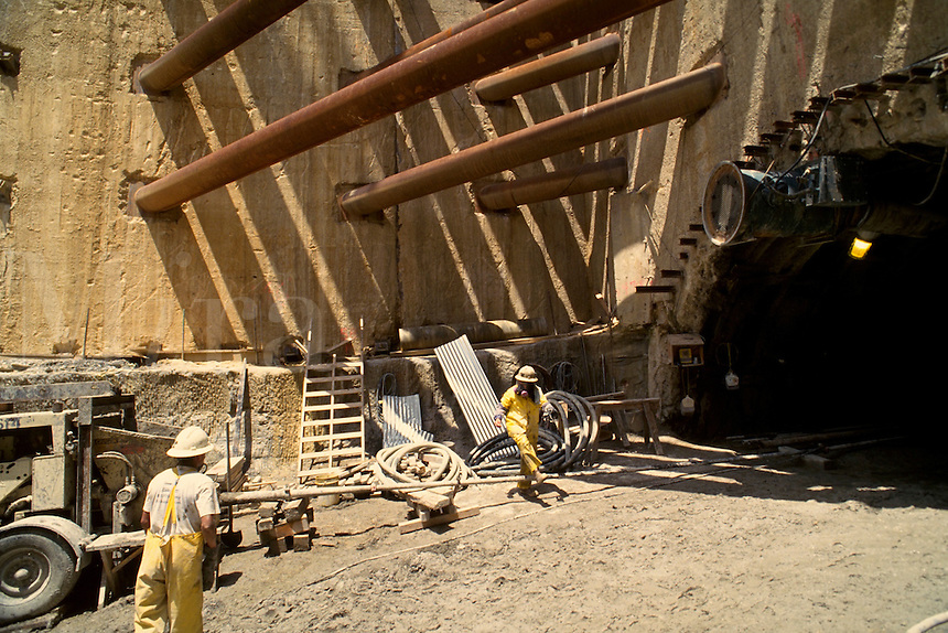 Site showing workers at the wall support near the entrance to a tunnel.